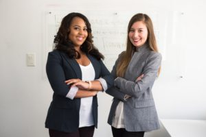 business women standing in front of a white board